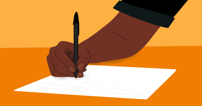A hand writes a letter on a table