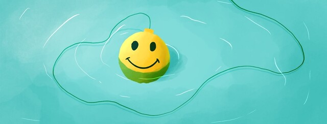a yellow fishing bobber with a smiley face floating in the water